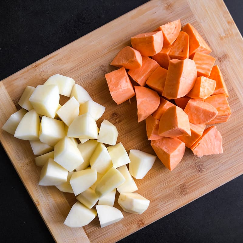 Russet and sweet potatoes chopped on a wood cutting board.