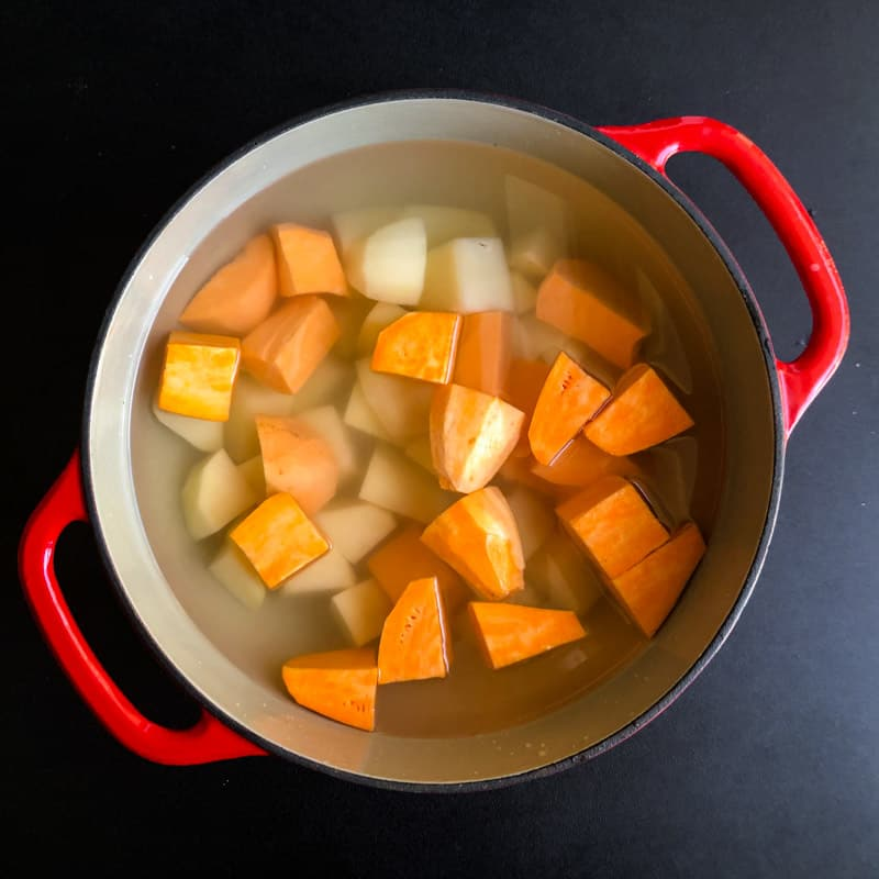 Chopped potatoes in a Dutch oven ready to boil on the stove top.