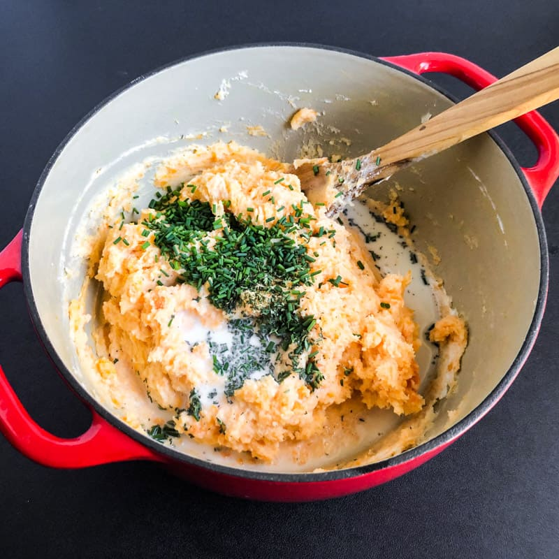 Fresh herbs, salt and pepper, and milk added to mashed potatoes.