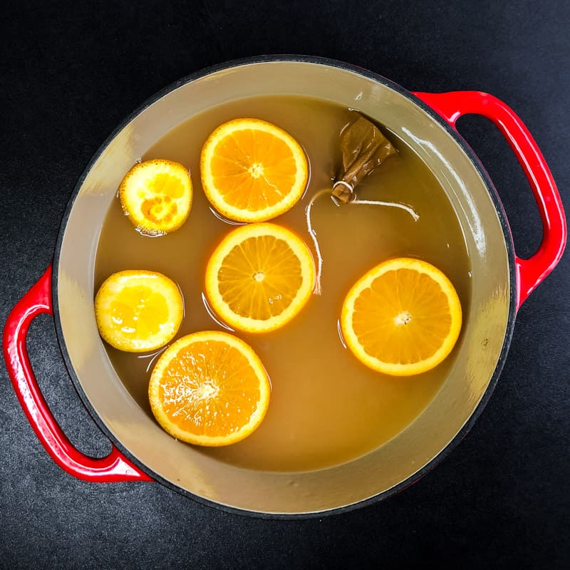 Overhead shot of Dutch oven filled with apple cider with orange slices floating and spices tied in a coffee filter.