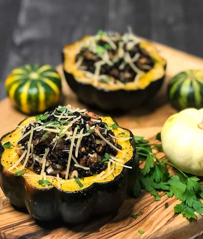 Side view close up shot of Vegetarain Stuffed Acorn Squash on a wood cutting board garnished with parmesan cheese and parsley with mini pumpkins in background.