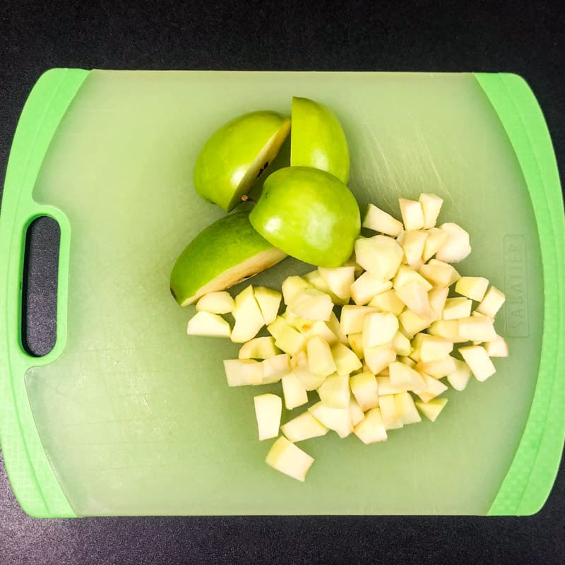Diced apples on a green cutting board.