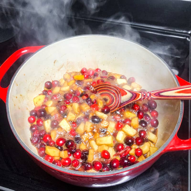 Apples and cranberries simmering in a Dutch oven.