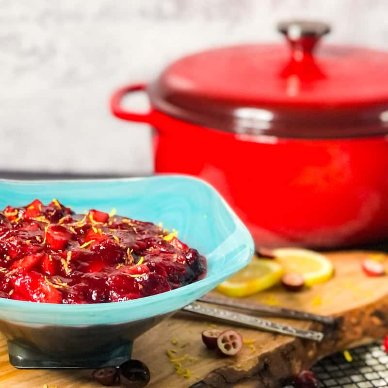 Cranberry Sauce in a blue bowl with a red Dutch oven blurred in the background.