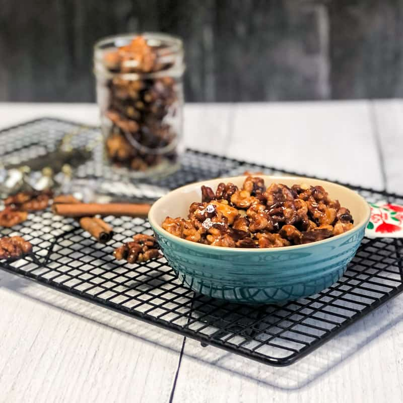 Maple Glazed Walnuts in a small turquoise bowl with a jar or more nuts blurred in background.
