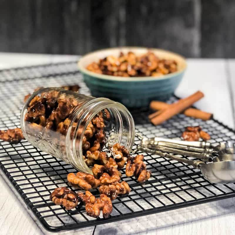 Mason jar of Maple Glazed Walnuts lying on the side with nuts spilling out and a blurred bowl of more nuts in the background.