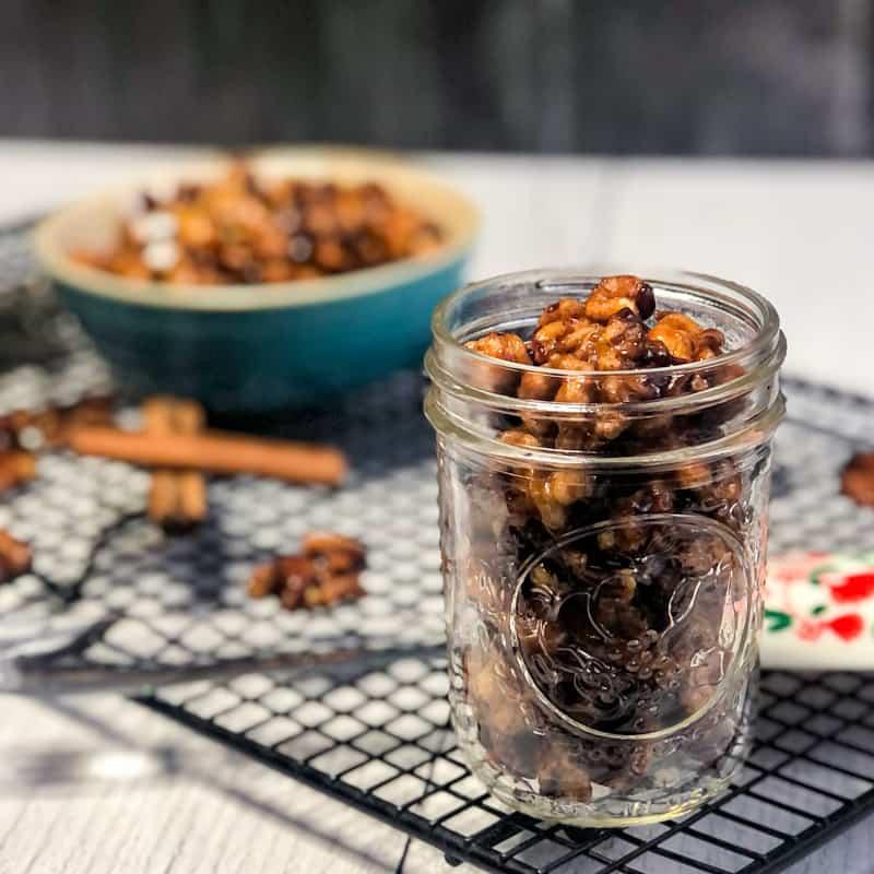 Maple Glazed Walnuts in a small mason jar with blurred bowl of glazed walnuts in background.