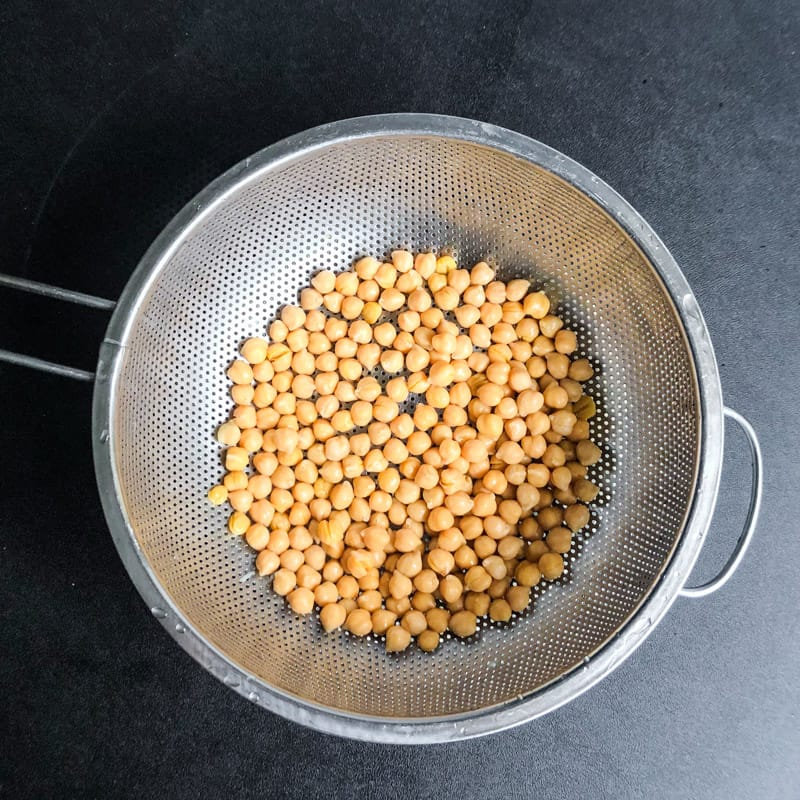 Drained and rinsed chickpeas in a metal colander.