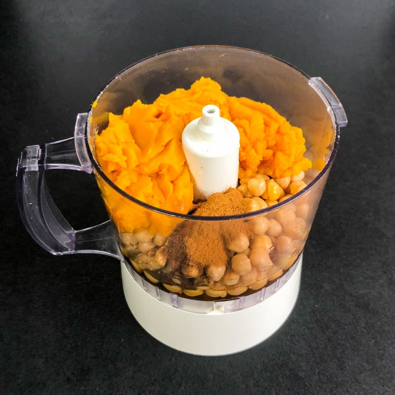 Chickpeas, pumpkin puree, aquafaba, vanilla, maple syrup, and spices in the bowl of a food processor ready to be blended.