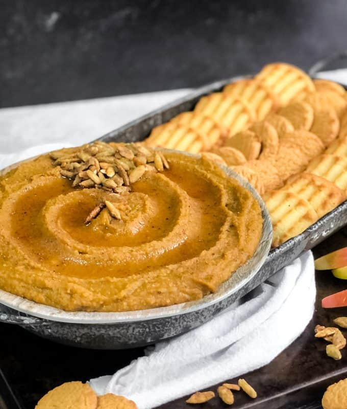Side shot of Pumpkin Pie Dessert Hummus swirled on a plate drizzled with maple syrup and garnished on the side with cookies and apples for dipping.
