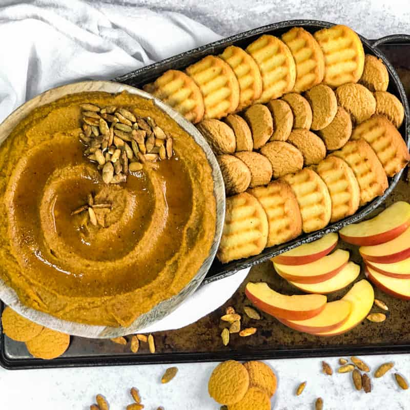 Overhead shot of Pumpkin Pie Dessert Hummus swirled on a plate drizzled with maple syrup and garnished on the side with cookies and apples for dipping.