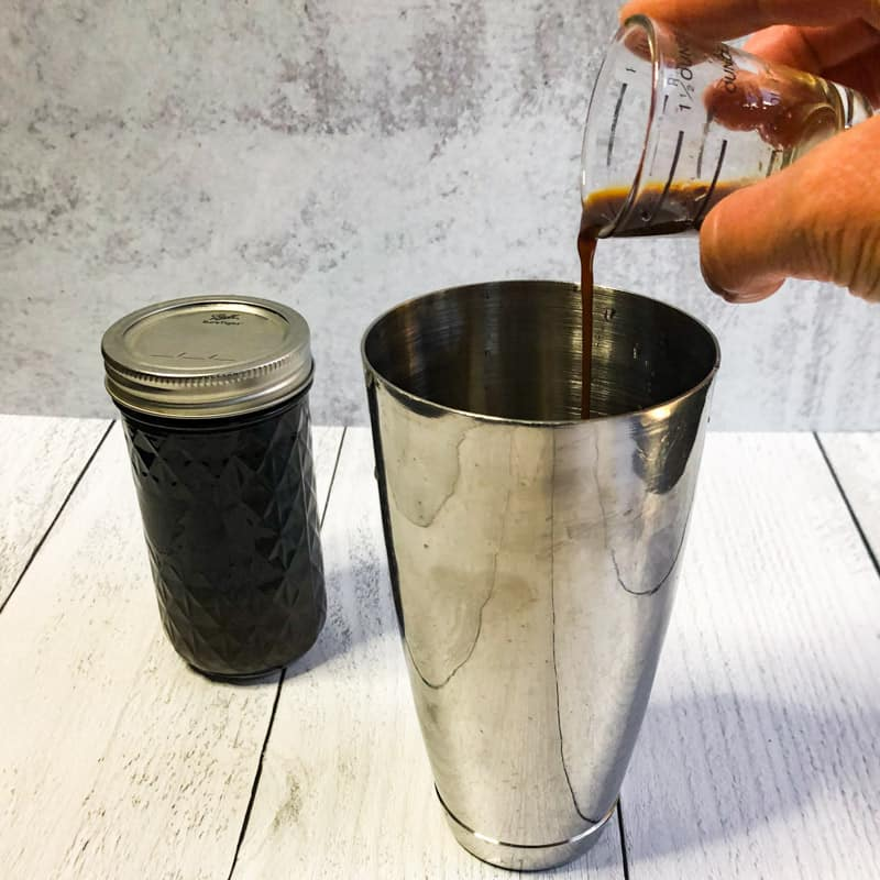 Pouring the simple syrup into the stainless shaker.