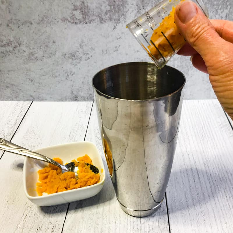 Adding the pumpkin puree to the stainless shaker.