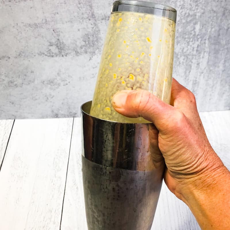 Hand holding a stainless shaker with a pint glass lid to mix the martini.