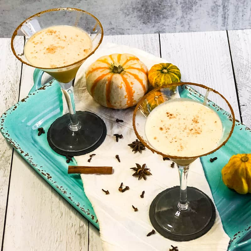 Overhead shot of Pumpkin Spice Martinis on a blue tray garnished with small pumpkins.