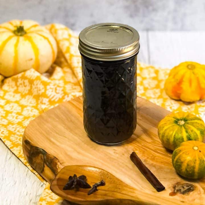 Jar of simple syrup on a wood platter with small pumpkins in background.