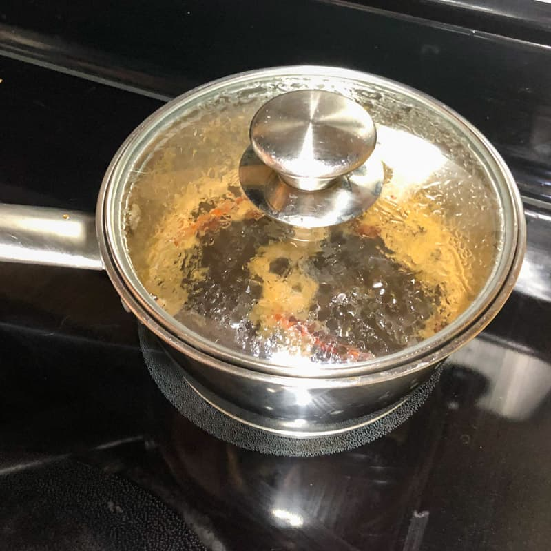 Covered sauce pan simmering on the stove to infuse the simple syrup.