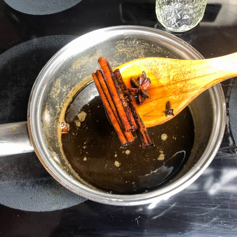 Straining out the whole spices with a wooden spoon after the simple syrup has cooled to room temperature.