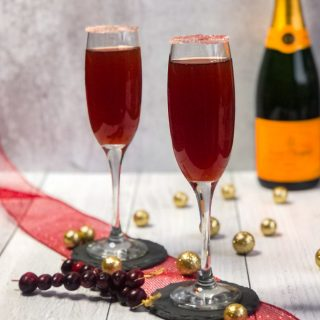 Cranberry Mimosas with a sugar rim and champagne bottle blurred in background.