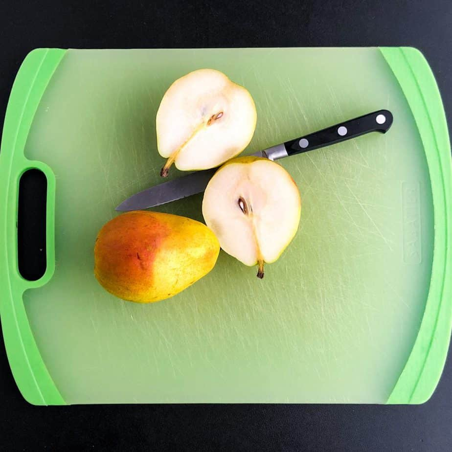 Pear sliced in half on a green cutting board with a knife and whole pear next to it.