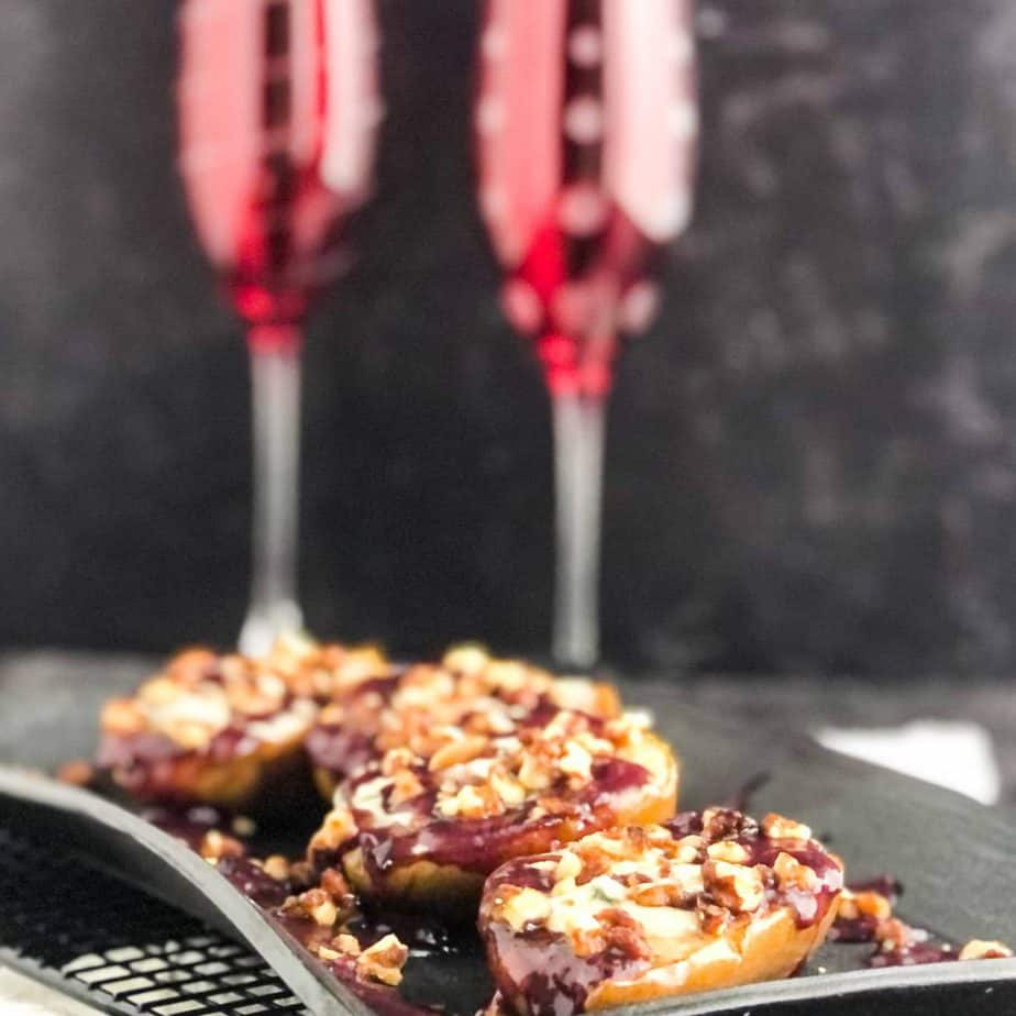 Close up shot of pears drizzled with blueberry sauce and topped with walnuts on a black platter with champagne glasses blurred in background.