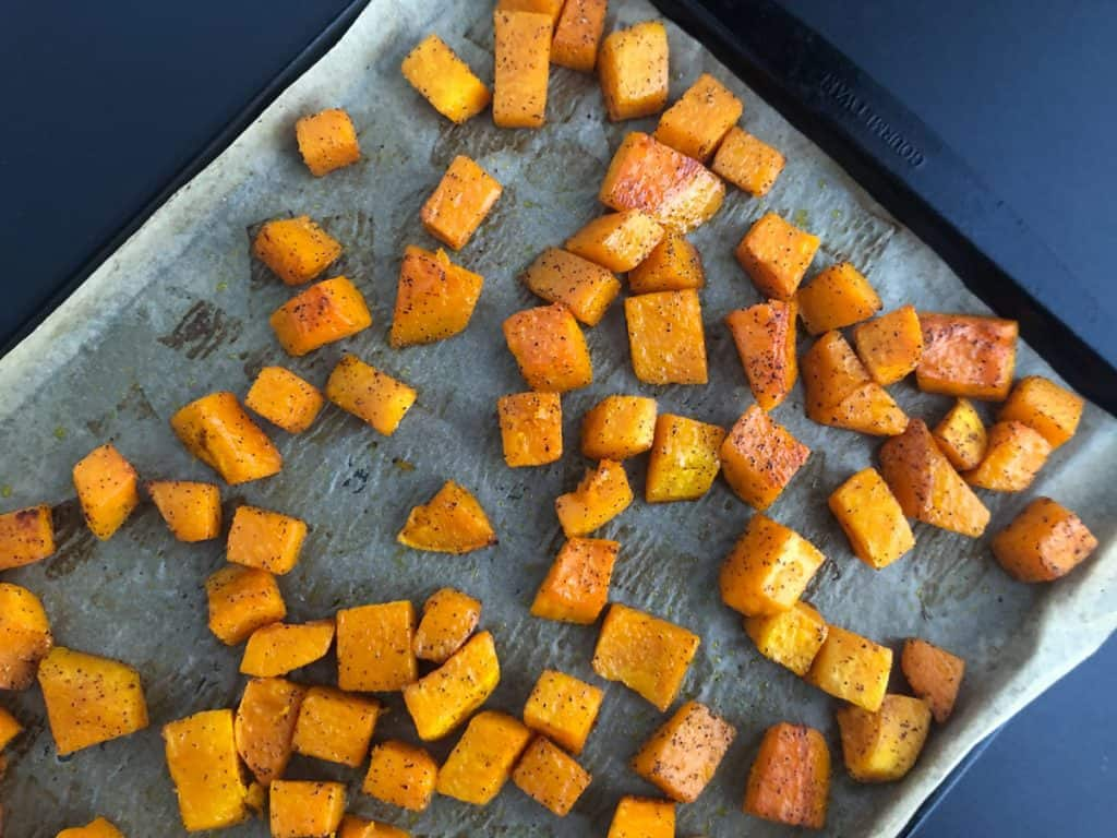 Oven roasted butternut squash on a parchment lined baking sheet.