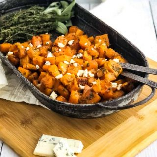 Close up of Roasted Butternut Squash garnished with gorgonzola cheese and fresh herbs to the side.
