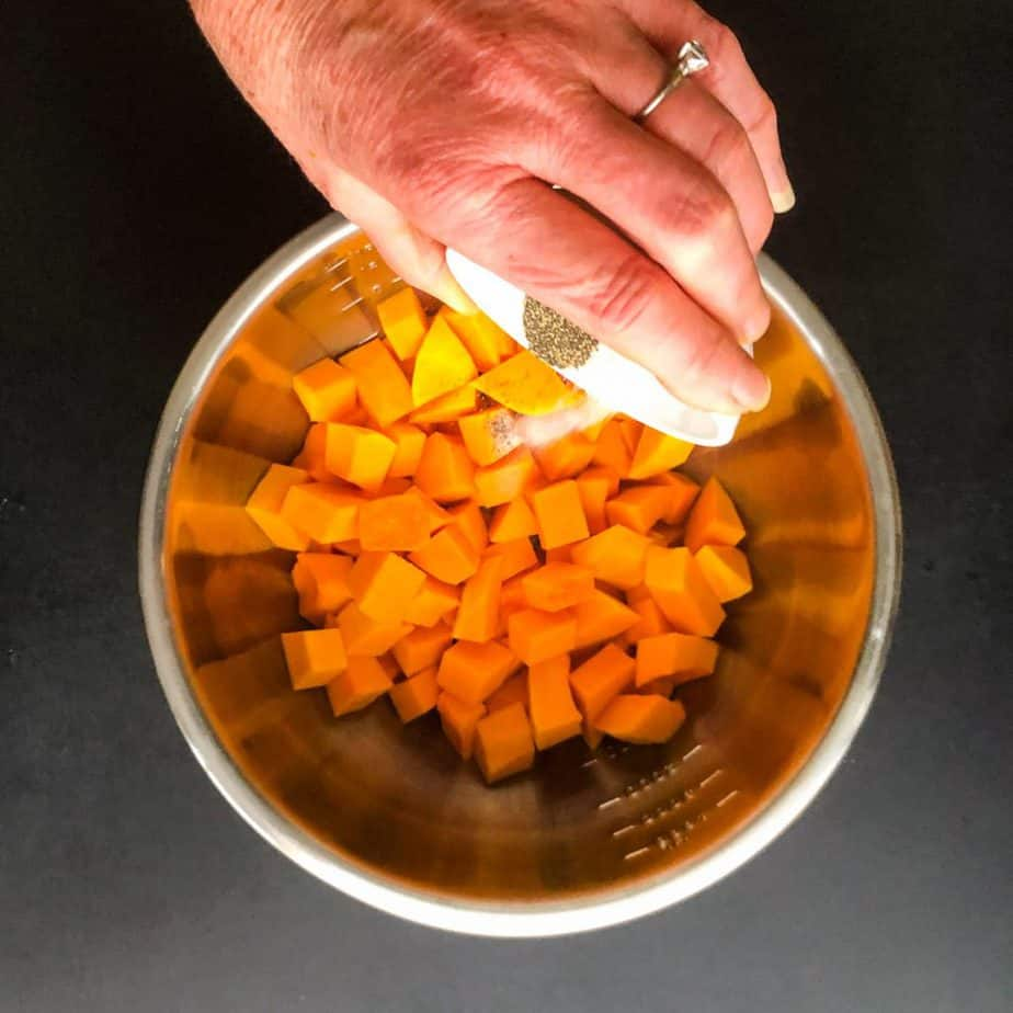 Diced squash in a stainless steel bowl with hand pouring in salt and pepper.