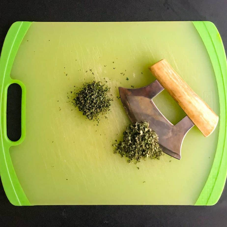 Finely chopped sage and thyme on a green cutting board.