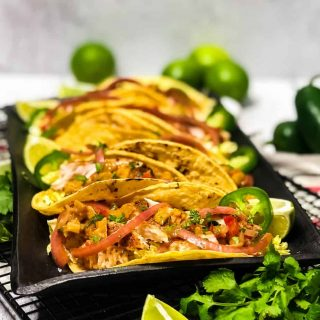 Close up shot of Blackened Fish Tacos on a black platter garnished with lime wedges and jalapeno slices.