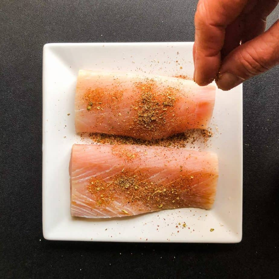 Hand sprinkling blackening seasoning on fish fillets on a white plate.