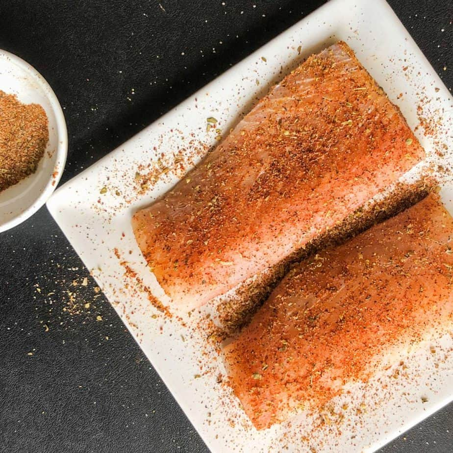 Seasoned fish fillets on a white plate with bowl of seasoning next to it.