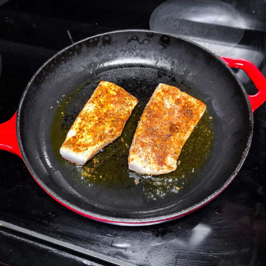 Seasoned fish fillets cooking in a cast iron skillet.