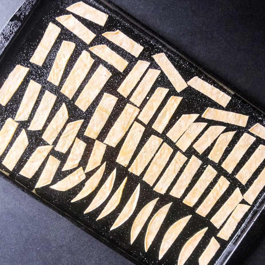 Tortilla strips placed on a prepared baking sheet ready to go in the oven.