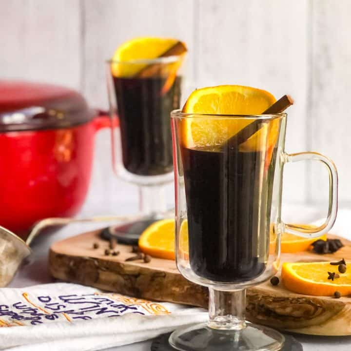 Two glass mugs of Mulled Cider garnished with orange slices and cinnamon sticks with red Dutch oven and more orange slices blurred in background.