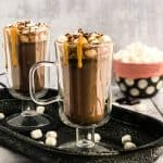 Close up shot of Peanut Butter Hot Chocolate in glass mugs on a metal serving platter, garnished with marshmallows, peanut butter sauce, and shaved chocolate with bowl of marshmallows blurred in background.