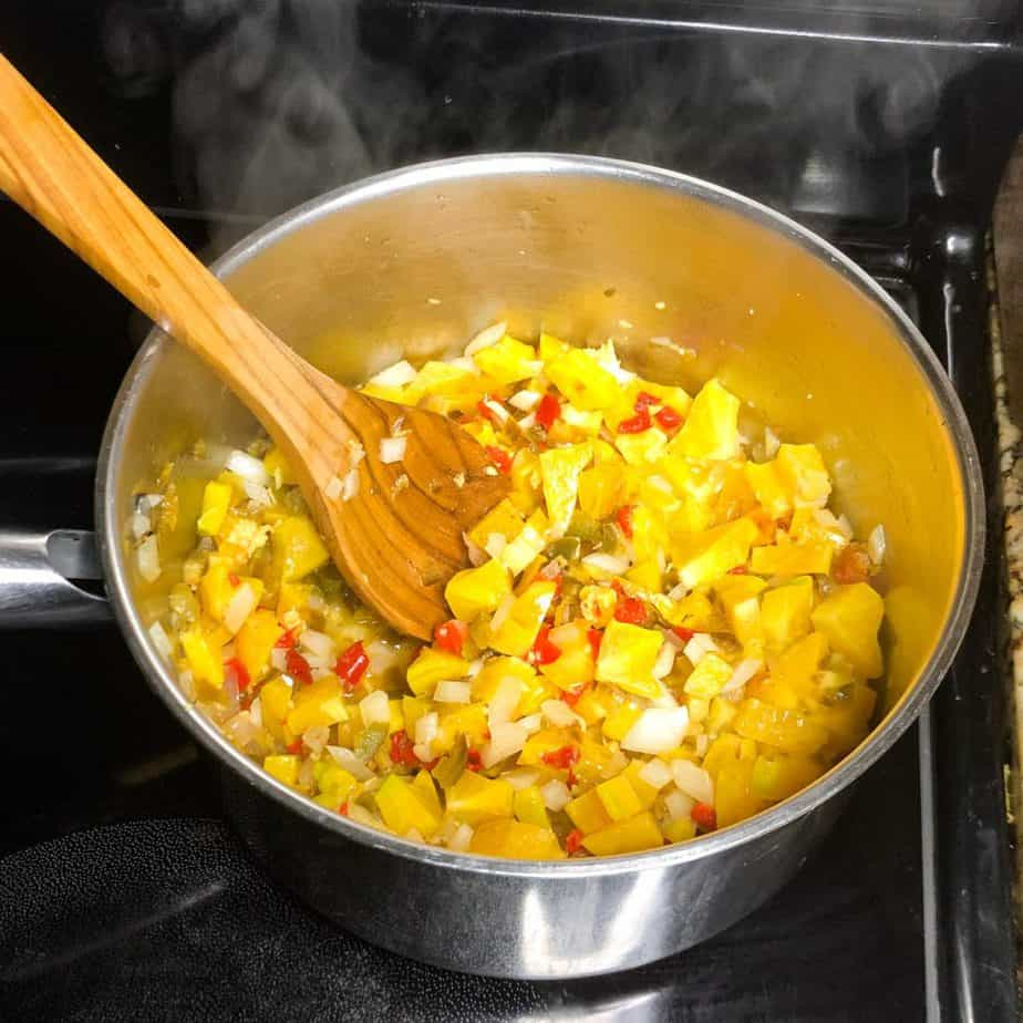 Wooden spoon stirring together the star fruit and veggies.