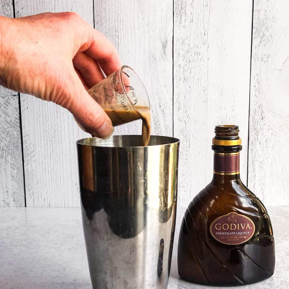 Hand pouring chocolate liqueur into a stainless steel tumbler.