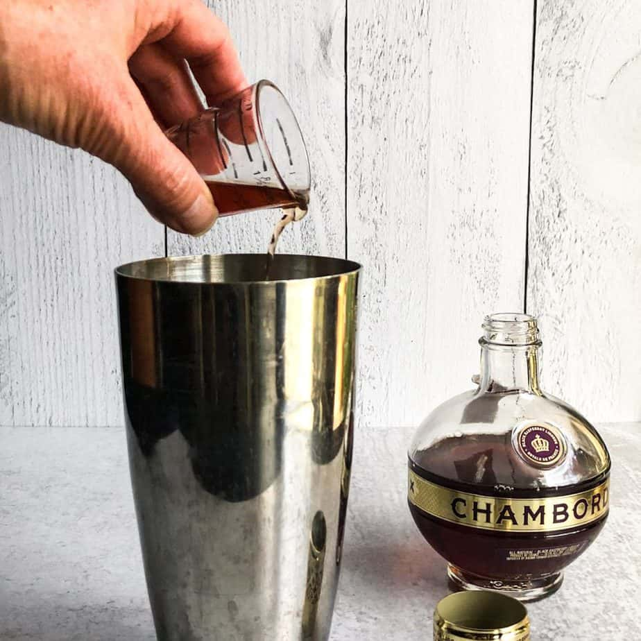 Hand pouring raspberry liqueur into a stainless steel tumbler.