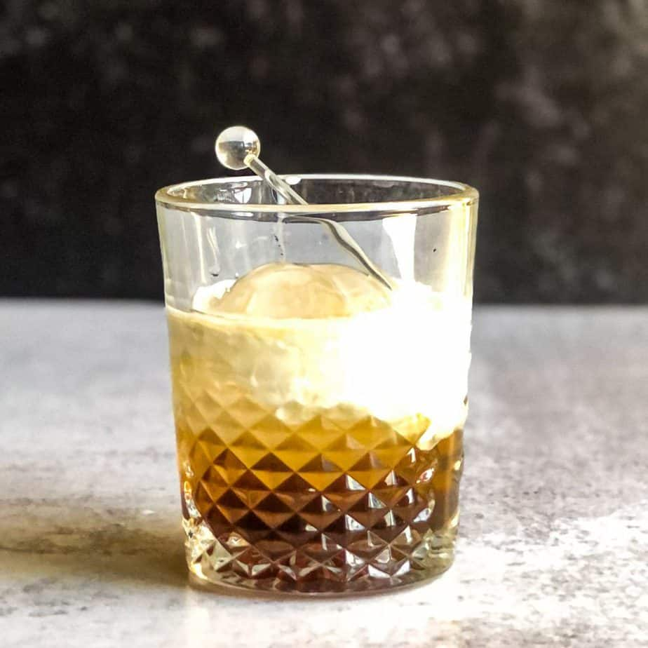 A finished Peanut Butter White Russian garnished with a glass stir stick.