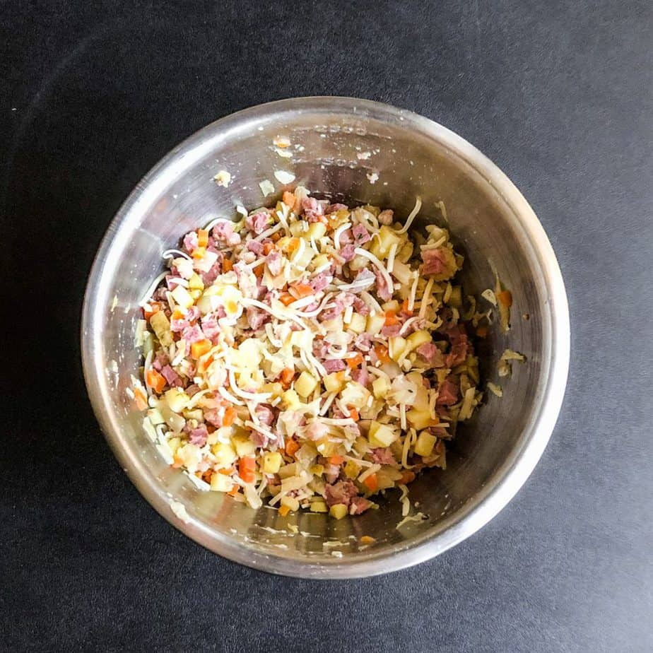 Ingredients for egg roll mixture fully combined in a stainless steel bowl.