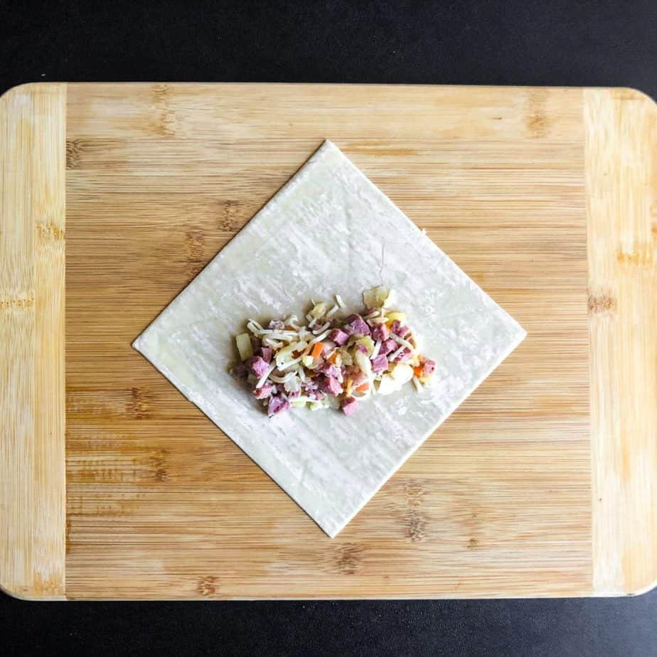 Egg roll wrapper with corned beef mixture placed in a log form.