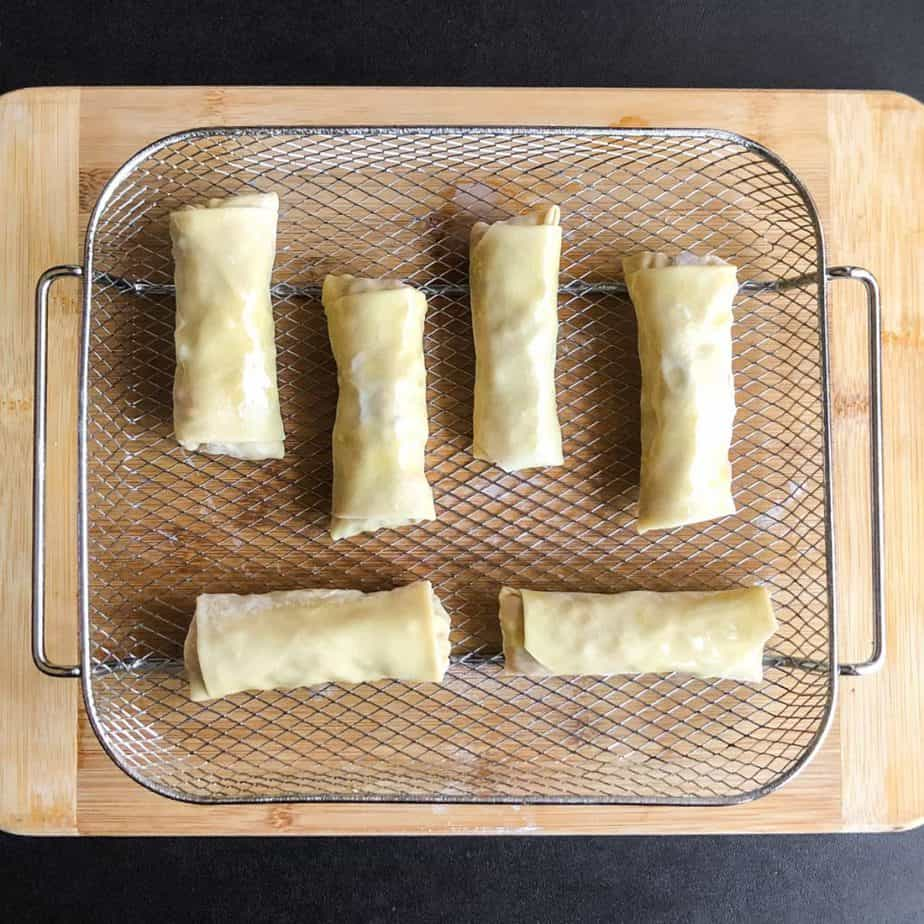 Prepared egg rolls in a fry basket ready to be air fried.