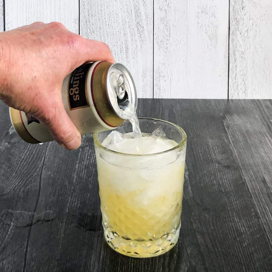 Hand pouring ginger beer into a glass.