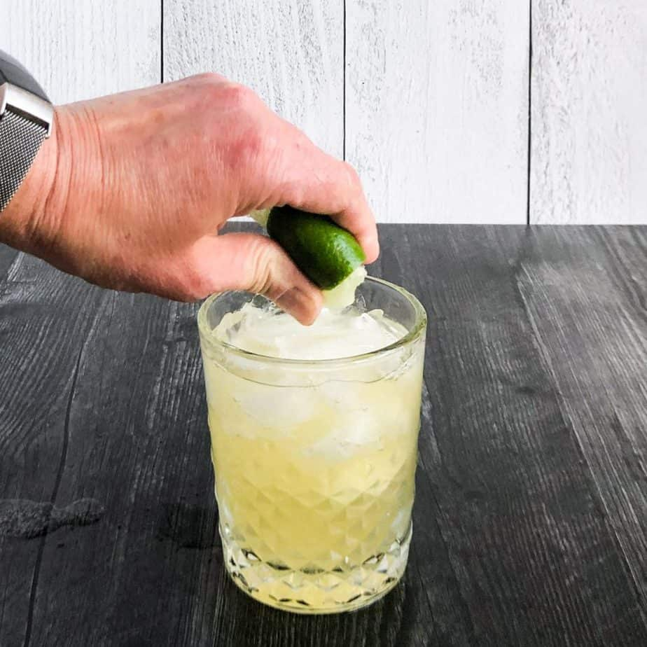Hand squeezing a lime quarter into the cocktail.