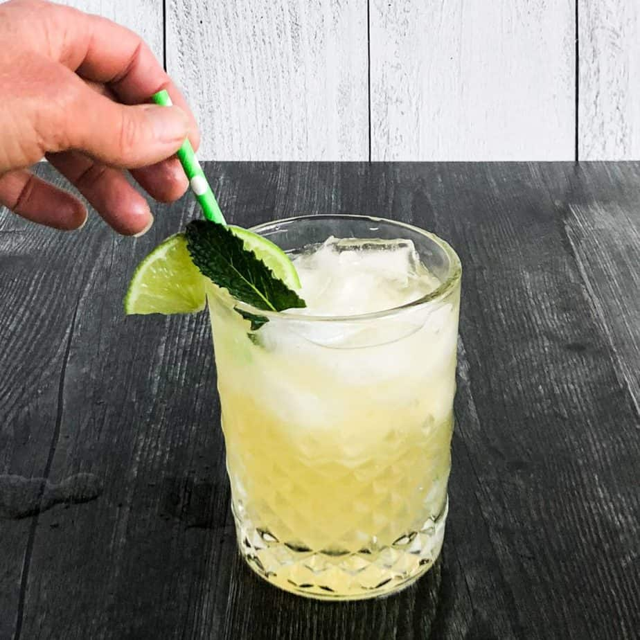 Hand garnishing the cocktail with a stir straw, mint leaf, and lime wheel.