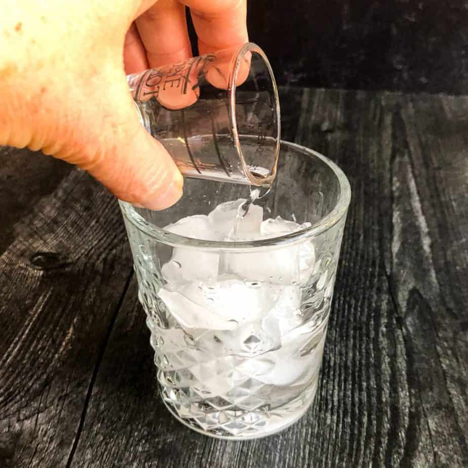 Hand pouring a shot of vodka into the rocks glass.