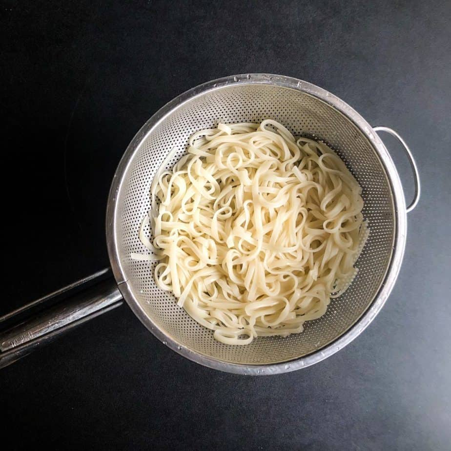 Cooked and drained rice noodles in a stainless steel colander.