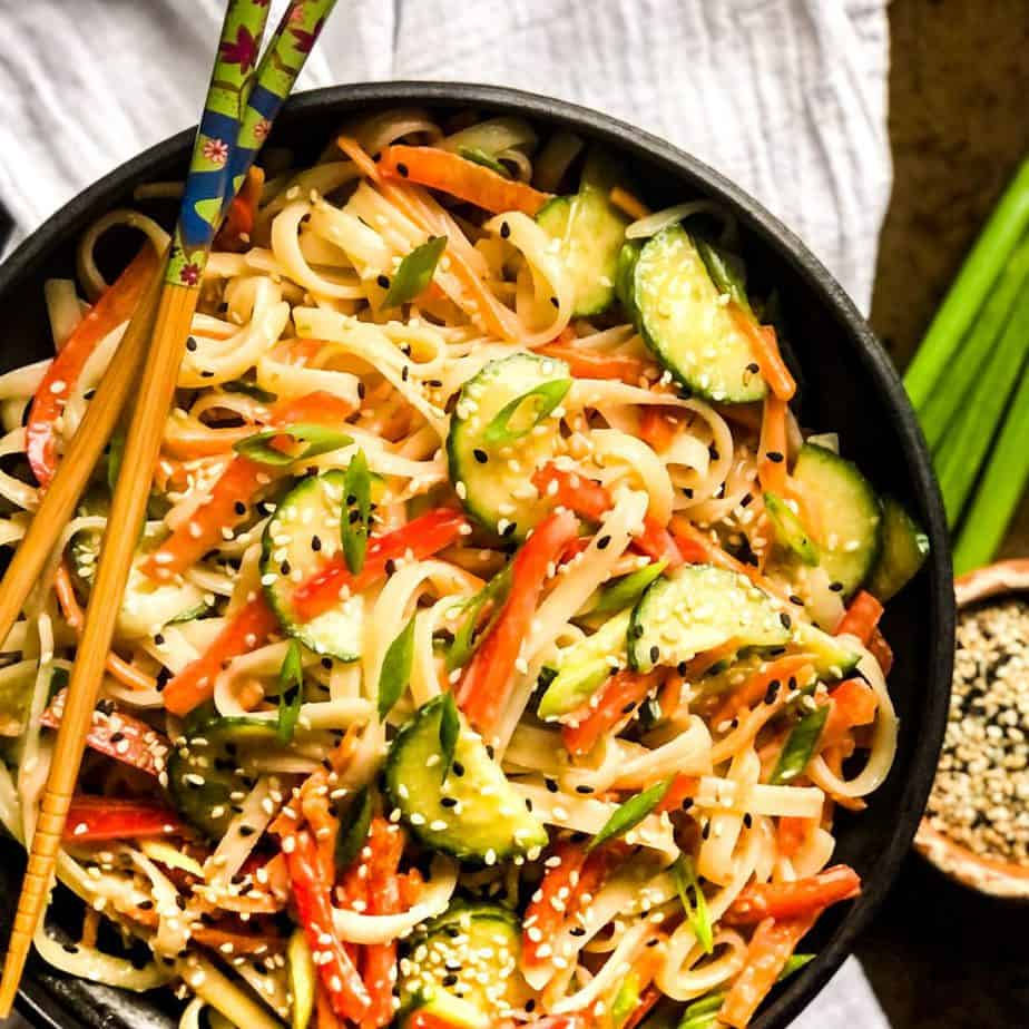 Overhead shot of rice noodle salad in a black bowl with chop sticks resting on top.