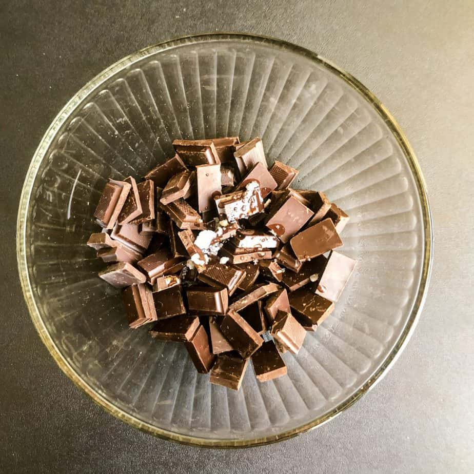 Glass bowl with chocolate pieces and coconut oil ready to go in the microwave.